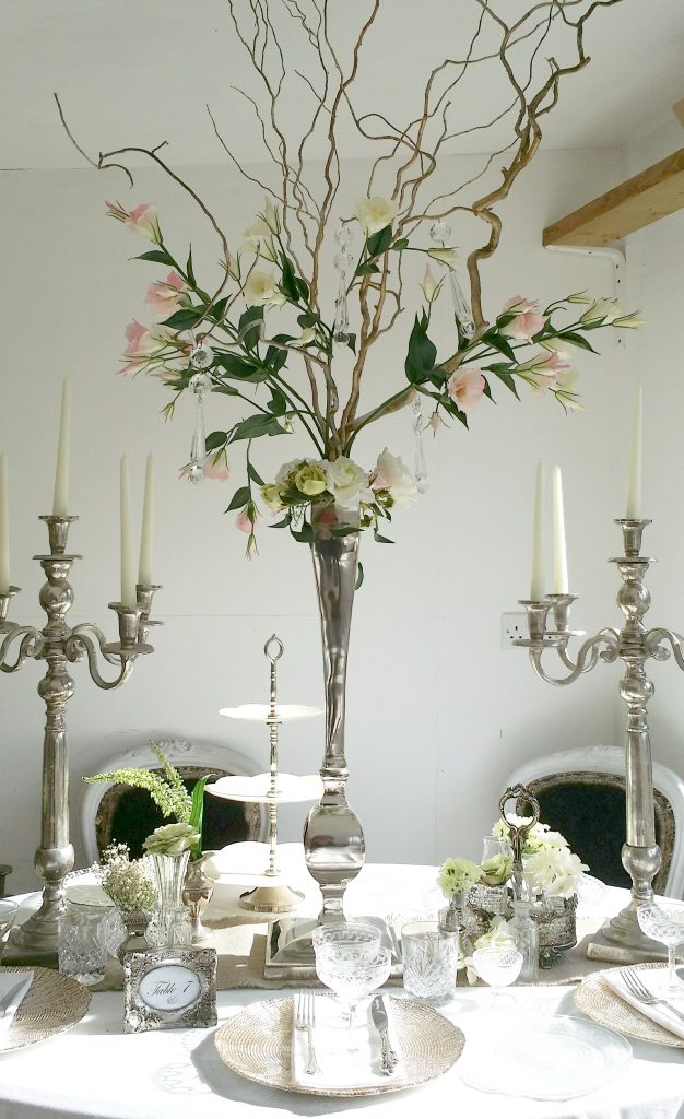 tall wedding table centres with tall silver candelabras , & vintage glasses