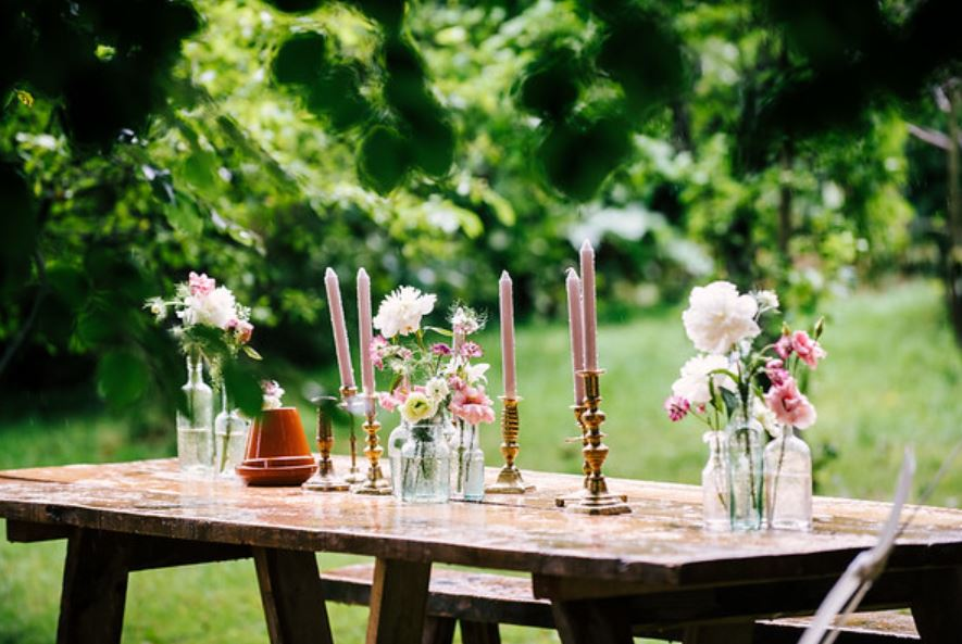 Hire of vintage glass bottles and gold brass candlesticks for a summer woodland wedding