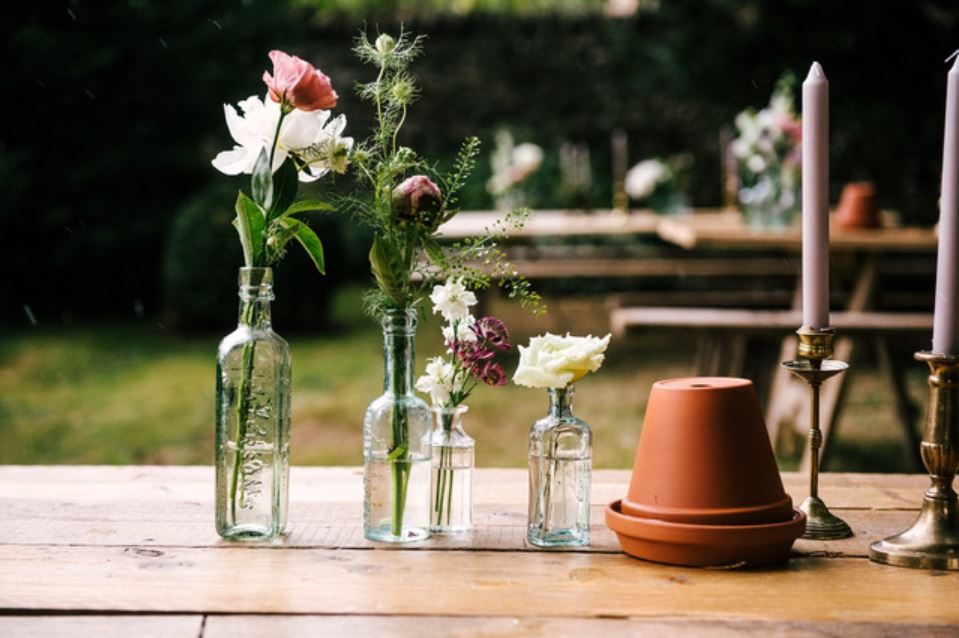 hire gold candlesticks, brass candlesticks & vintage bottles for vases for Cotswold woodland and summer wedding in Burford