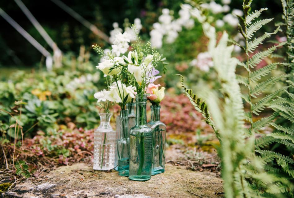 mix of vintage clear and aqua green bottles for flowers at woodland inspired weddings