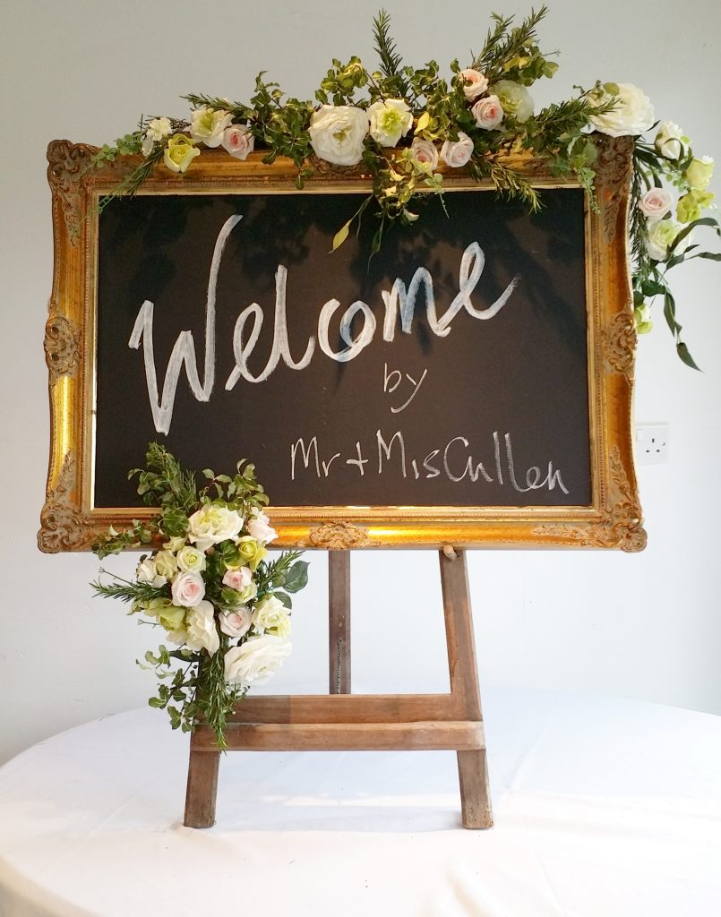 gold frame blackboard on easel with flowers for wedding & event hire