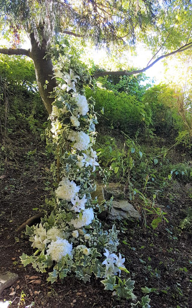 garland of wedding flowers draped in a tree as decor at a woodland wedding